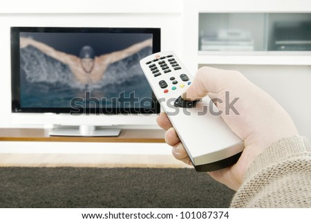 Man's hand holding a tv remote control, pressing a button while pointing at a flat screen tv. - stock photo