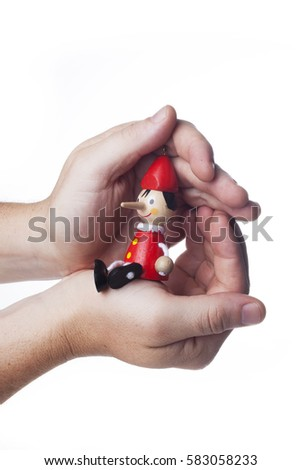 Man's hand holding a wooden Pinocchio doll.