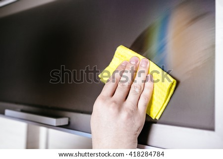 Man's hand holding a yellow rag and cleaning furniture in the kitchen - stock photo