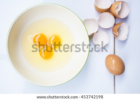 Man's hand holding an egg and starts preparing omelet. Key ingredient for tasty omelet. Hand separates white from yolk. Ingredient for high-protein dish.  - stock photo