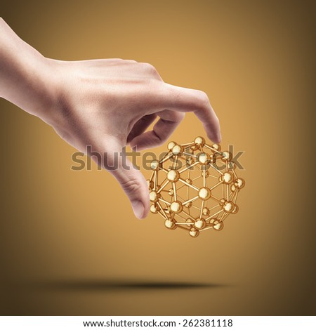 Man's hand holding atomic molecule. High resolution 3D collection of gold objects - stock photo