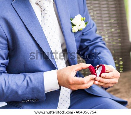 Man's hand holding engagement ring - stock photo