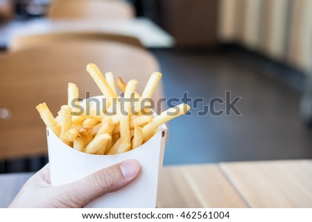 Man's hand holding French fries in a white carton box in restaurant
