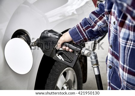 Man's hand holding gas nozzle while  pumping gas into parked vehicle - stock photo