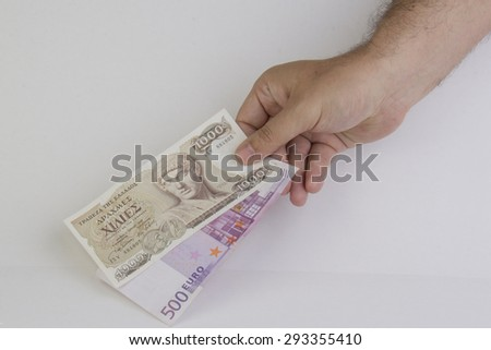 Man's hand holding greek and european money