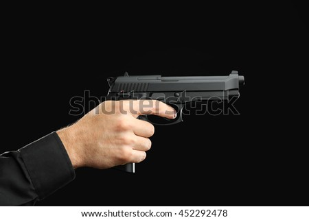 Man's hand holding gun on black background - stock photo