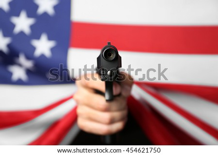 Man's hand holding gun on star and stripes background - stock photo