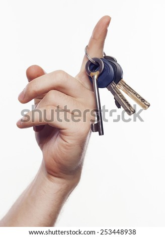 Man's hand holding keys over white background - stock photo