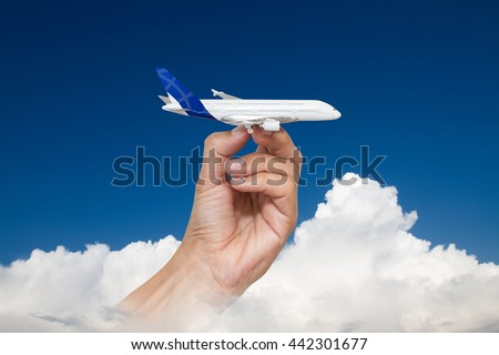 Man's hand holding model of airplane against sky with cloud background.