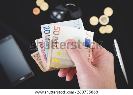 man's hand holding money on the black background - stock photo