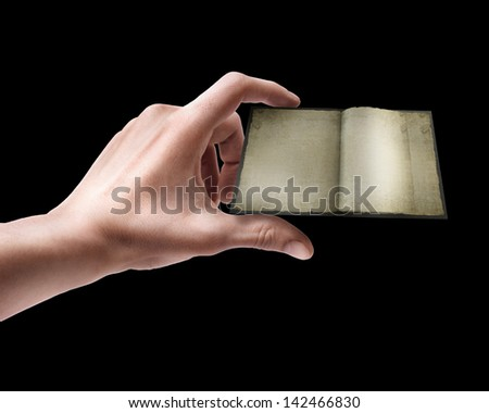 Man's hand holding Old opened book isolated on black background - stock photo