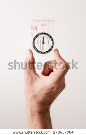 man's hand holding out a compass showing him the way shot in the studio - stock photo