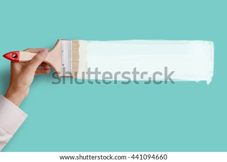 Man's hand holding paintbrush paint white color on blue aqua color wall, blank space for your text, banner, copyspace, advertising, or your design.  - stock photo