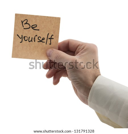 man's hand holding reminder of the necessary be yourself isolated white