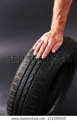 Man's hand holding tyre on dark background