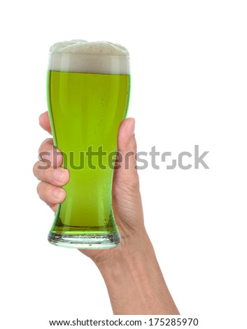 Man's hand holding up a glass of foamy green beer to celebrate St. Patrick's Day. Vertical format over a white background - stock photo