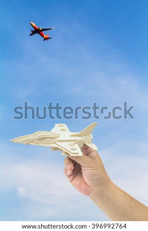 Man's hand holding wooden airplane against blue sky and real airplane