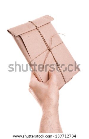 Man's hand holds envelope tied with a rope isolated on white background - stock photo