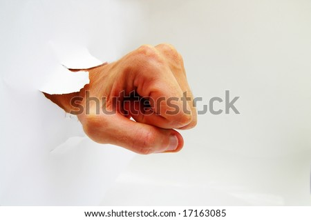 man's hand in a fist punching through a hole - stock photo