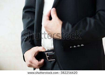 Man's hand in suit holding the belt