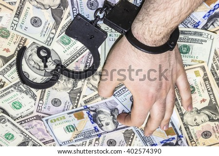 Man's hand is in metal handcuffs on background of dollars - stock photo
