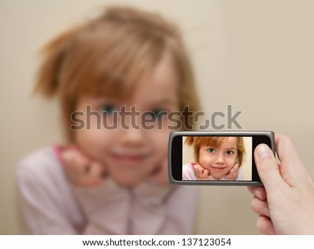 Man's hand making photo of a little girl with a mobile phone. Selective focus on a mobile phone with a portrait of a girl. - stock photo