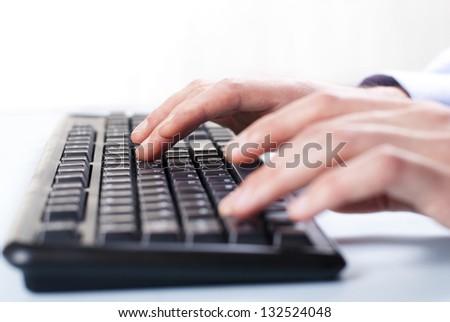 man's hand on computer keyboard - stock photo