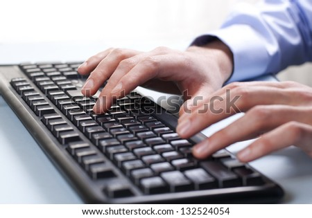 man's hand on computer keyboard - stock photo