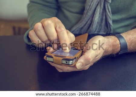 Man's hand on iphone sending a message - stock photo