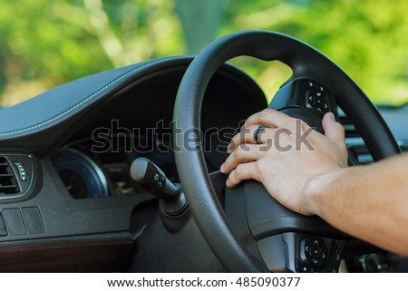 Man's hand on the steering wheel of a car wheel driver car