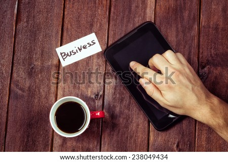 Man's hand on the tablet. Man's hand, a computer and a cup of black coffee on the table. Young businessman at work. Work with a cup of coffee. The concept of Digital Business. - stock photo