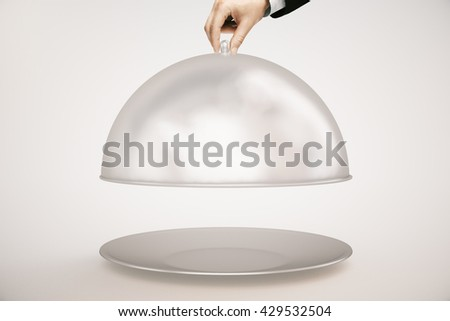 Man's hand opening silver cloche on light background. Mock up, 3D Rendering - stock photo