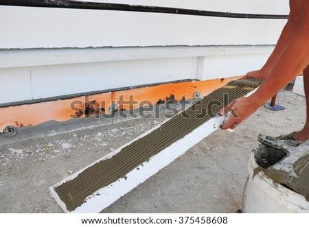 Man's Hand Plastering a Wall Styrofoam or Foam Board Insulation.  Styrofoam Insulation for Basement Walls. House Insulation. - stock photo