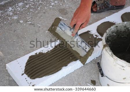 Man's Hand Plastering a Wall Styrofoam or Foam Board Insulation with Trowel. Styrofoam Insulation for Basement Walls. Installing Rigid Foam Insulation Board is Easy - stock photo