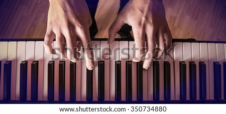 Man's hand playing piano.  - stock photo