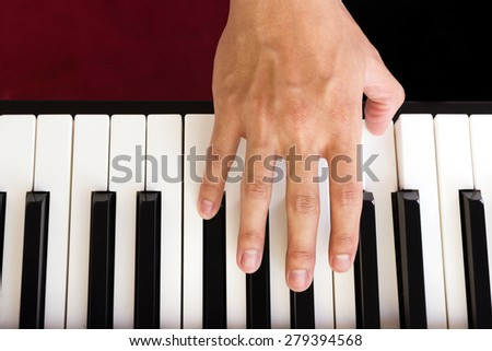 Man's hand playing piano. Top view.
