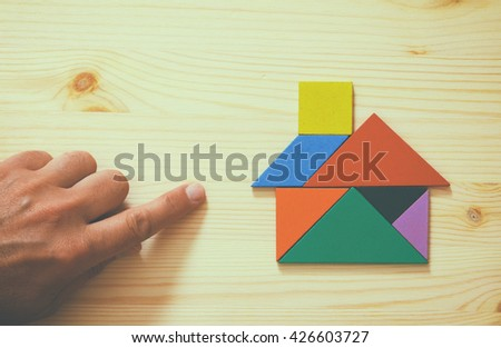 man's hand pointing at house made from tangram puzzle over wooden table. retro style image