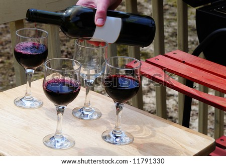Man<s hand pouring wine into glasses in a BBQ party