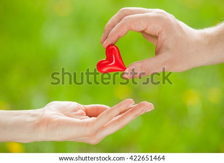 Man's hand proposing a red heart to woman's hand, light green background