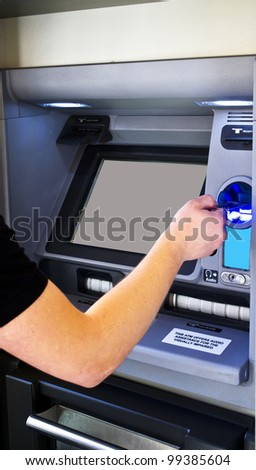 man's hand puts bank card into ATM - stock photo