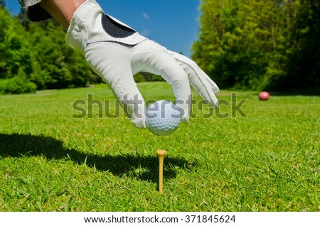 Man's hand putting a golf ball on the tee with a beautiful golf course as a background. - stock photo