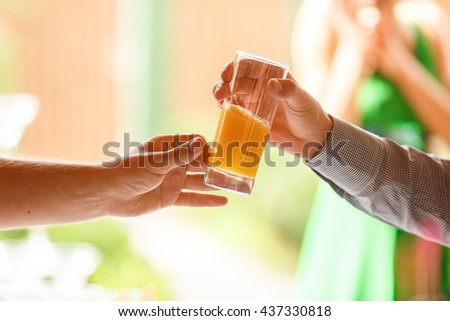Man's hand reach out a glass with fresh juice to another man - stock photo