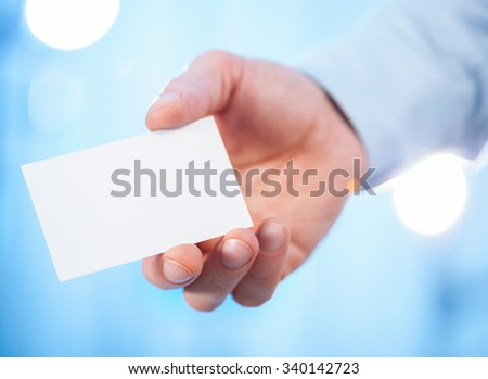 Man's hand reaching out a business card - closeup shot