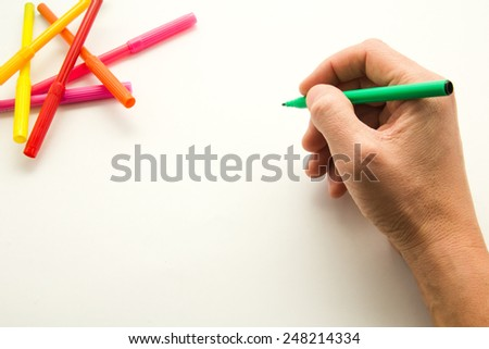 man's hand ready to draw a sketch of felt-tip pen