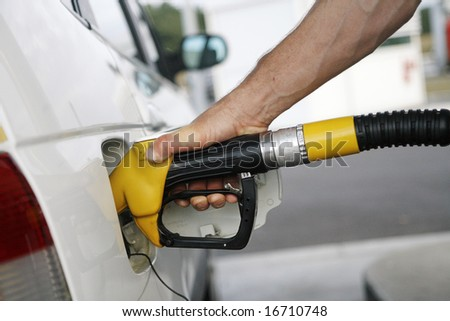 man's hand refilling the car with a gas pump
