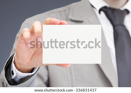 Man's hand showing business card.