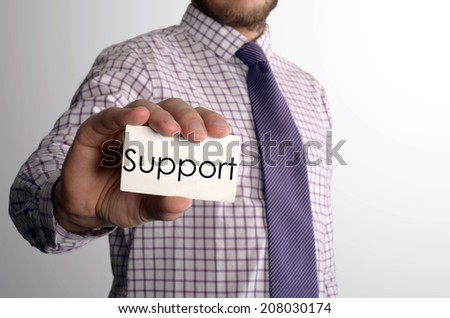 Man's hand showing business card with text Support - closeup shot on grey background  - stock photo