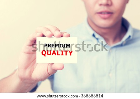 Man's hand showing PREMIUM QUALITY text on the card business card - closeup shot on white background. - stock photo