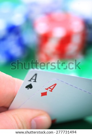 Man's hand showing two ace card token in bakcground - stock photo