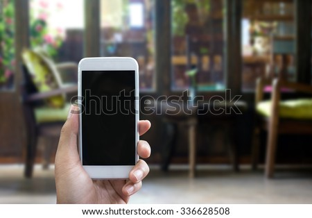 Man's hand shows mobile smartphone in vertical position, blurred background - mockup template - stock photo
